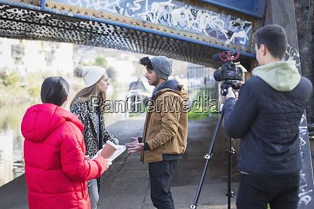 young adults vlogging under urban bridge