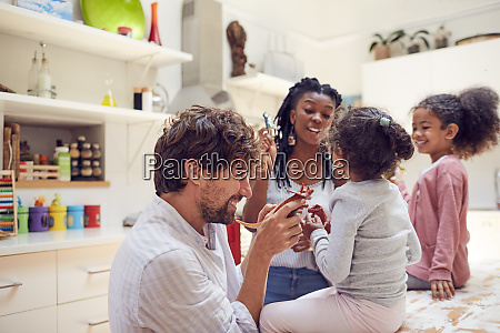 young family playing with toy dinosaurs