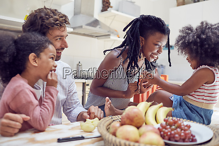 young family eating fruit on table