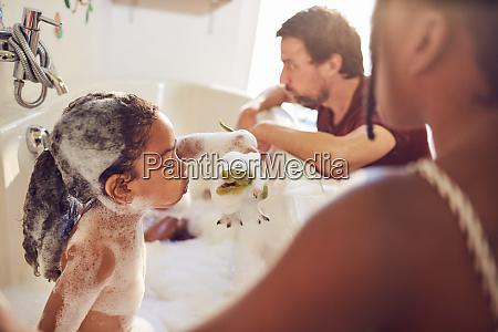 parents giving daughters bubble bath