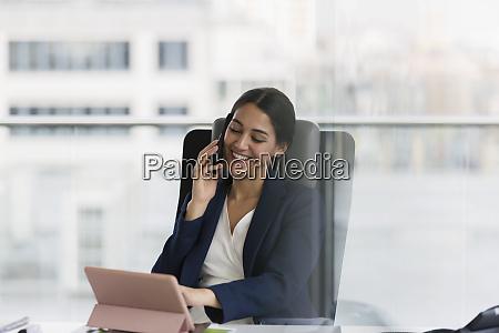 smiling businesswoman talking on smart phone