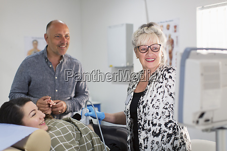 technician performing ultrasound for happy pregnant