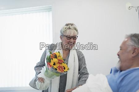 happy senior woman bringing flower bouquet