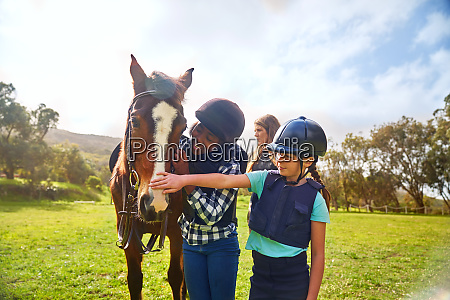 happy girls petting horse in sunny