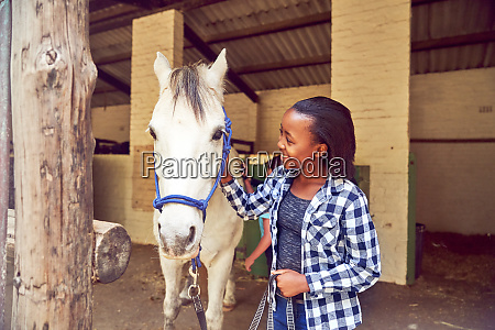 happy girl petting horse outside stables