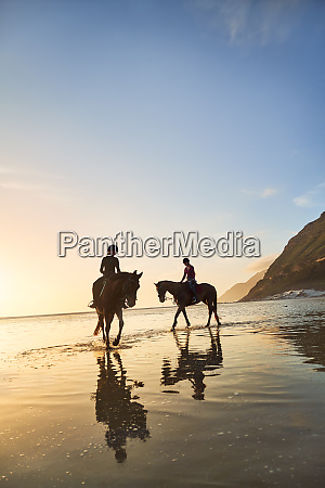 young women horseback riding on tranquil