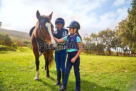 girls petting horse in sunny rural