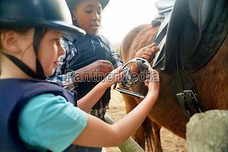 girls adjust stirrups preparing for horseback