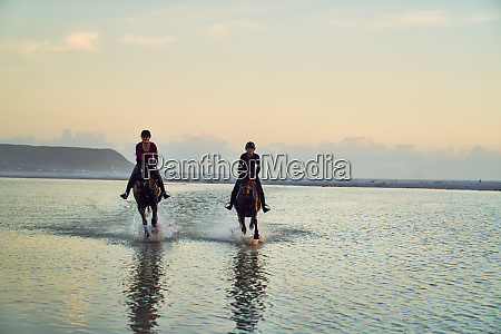 young women horseback riding in ocean
