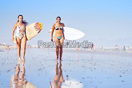 portrait confident young female surfers on