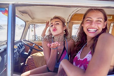 portrait playful young women friends blowing