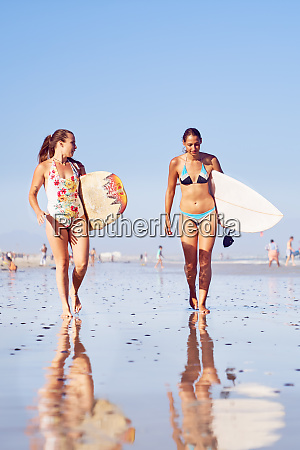 young female surfers with surfboards on