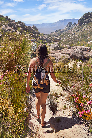 young woman hiking on sunny trail