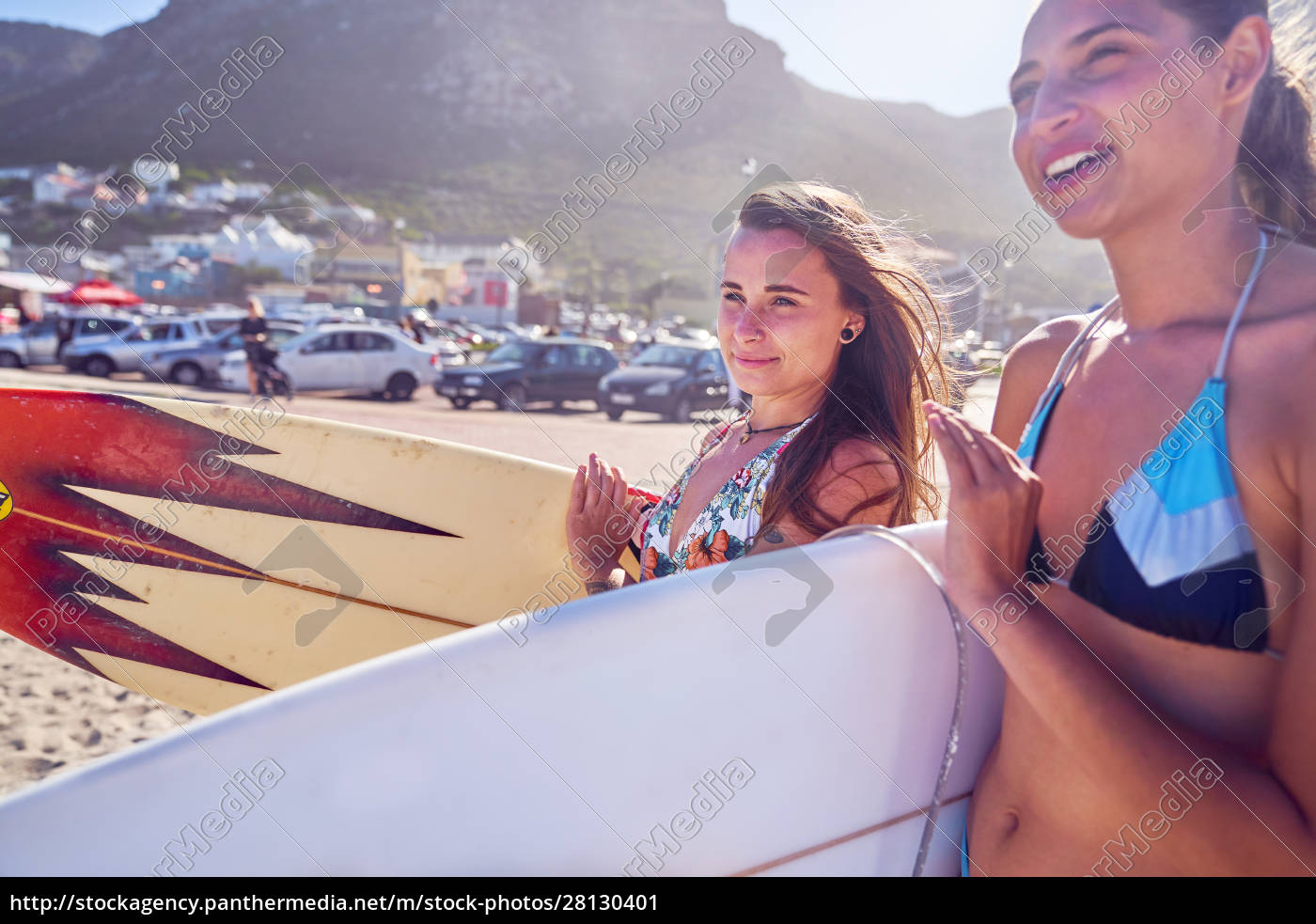 young, women, with, surfboards, on, sunny - 28130401