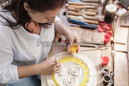 woman in woodcarving studio painting wooden