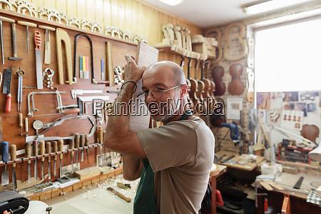violin maker checking sound of wood