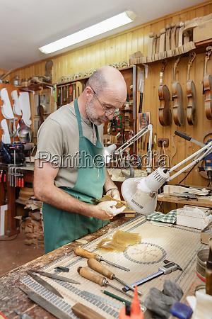 violin maker working on new instrument