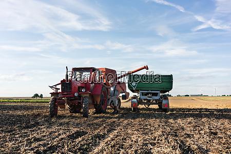 farmer adjusting combine trailer during grain