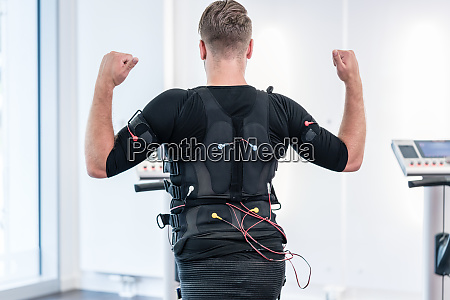 man in ems suit training his