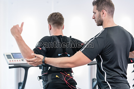 trainer helping man to do an