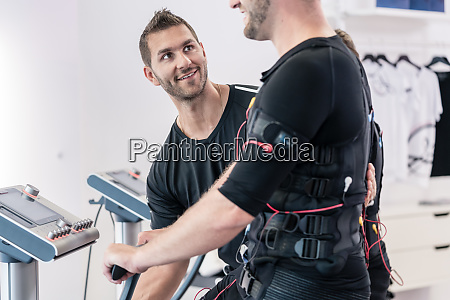 trainer helping man in ems gym