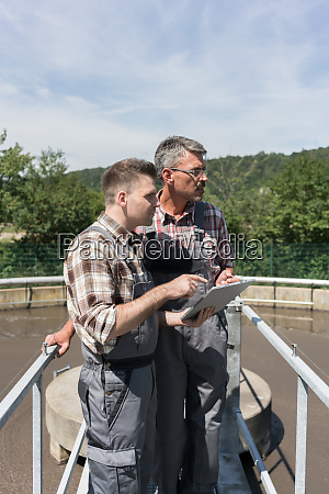 two engineers standing on bridge over