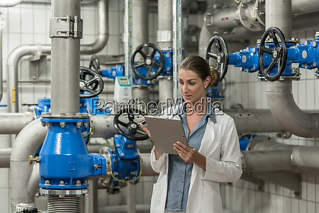 laboratory technician checking report on tablet