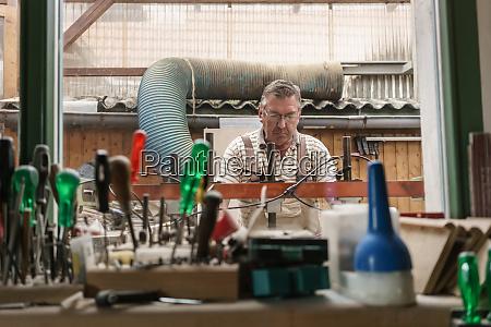 senior craftsman working in his wood