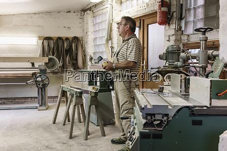 carpenter in his wood workshop putting