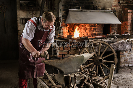 blacksmith working on pick with hammer