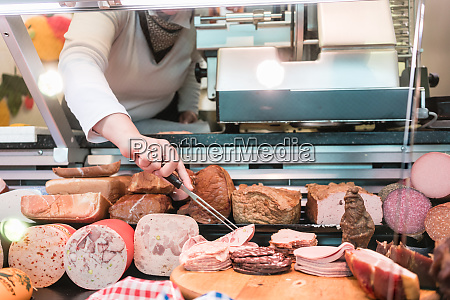 saleswoman in butchery taking meat out