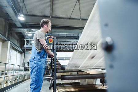 technician on printing press monitoring the