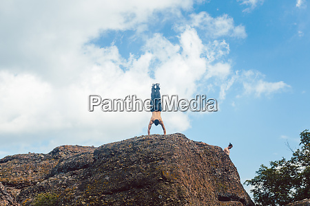acrobat doing handstand on a cliff