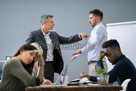 two male colleagues fighting in office