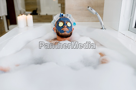 man applies face mask and relax