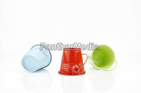 three metal buckets of different colours