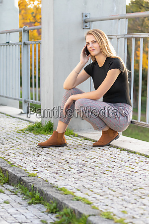 pensive young girl is squatting and