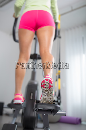 young womans muscular legs on steppertreadmill