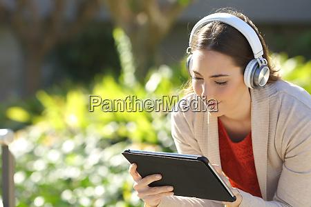 woman wearing headphones watching media on