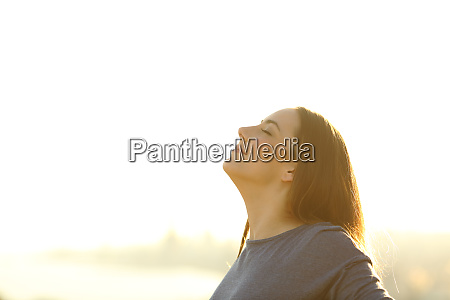 satisfied woman breathing fresh air standing