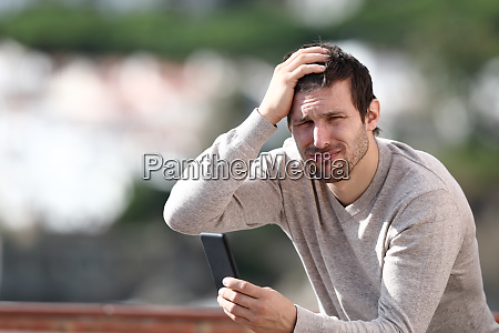 confused man holding mobile phone complaining