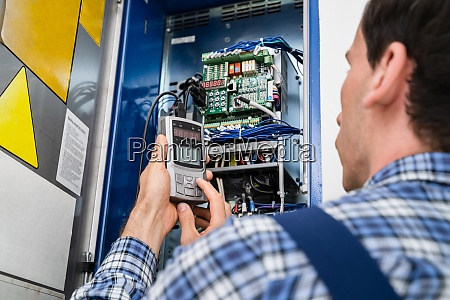 electrician checking fuse box