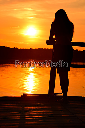 silhouette of young woman over sunset