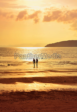 silhouette of two people on sunset