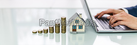 house and stack of coins on