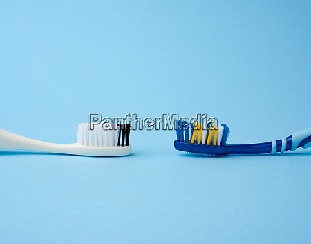 two plastic toothbrushes on a blue