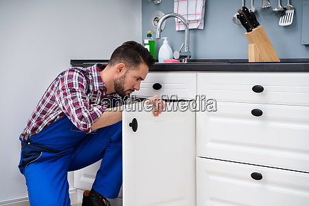 man in overall repairing cabinet