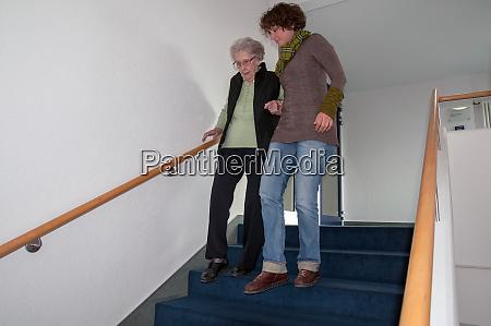 caregiver helps senior woman climbing the