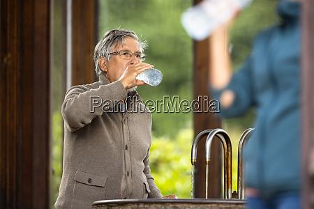 handsome senior man drinking mineral water