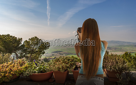woman taking photograph of hills